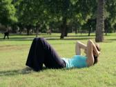 Stock Video Footage of Young sportswoman doing crunches, lying on grass in the park NTSC