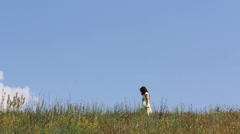 Fairy scenery, young lady walk on top hill and  pick flowers, blue serene sky Stock Footage