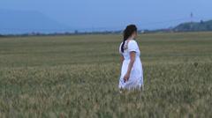 Young peasant woman walk in grain mature plain Stock Footage