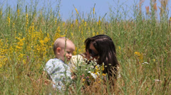 Lovely scenery, attractive baby and mother relax on flower field, lady kiss boy Stock Footage