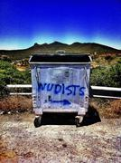 Nudists written on dumpster in rural landscape Stock Photos