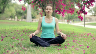 Stock Video Footage of Young woman meditating yoga on a grass in the park HD