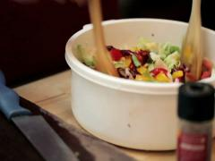Woman mixing salad with wooden spoons in plastic bowl NTSC Stock Footage
