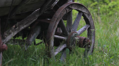 Focus on detail  old wooden wheel cart on new green spring grass Stock Footage