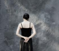 Japanese woman standing by gray curtain Stock Photos