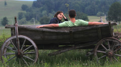 Romantic couple talking in nature, traditional wooden cart  Stock Footage