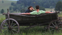 Couple of lover relax on traditional wooden cart Stock Footage