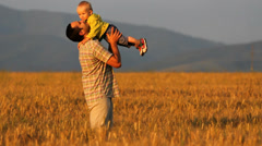 Father and baby son in golden grain culture field, warm evening light Stock Footage