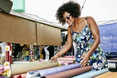 Mixed race woman examining fabrics at flea market Stock Photos