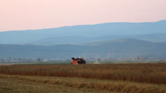 Thresher, threshing agriculture machine rich field at sunset Stock Footage