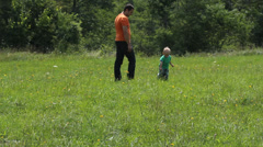 Attractive baby and father walk in spring  green meadow Stock Footage