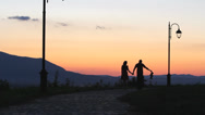 Stock Video Footage of Young parents and baby child silhouettes at dream sunset, walk together in park