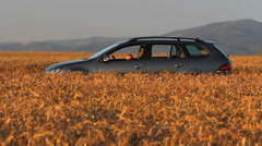 Blonde baby at the car wheel in the grain field at twilight, ready for car ride Stock Footage