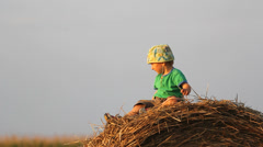 Sweet little baby boy on straw bale play with hay, vacation in nature Stock Footage