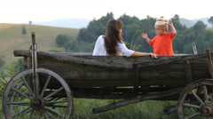 Young beautiful mother with baby child with traditional cap rest, old wood cart Stock Footage