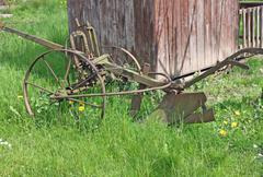 old rusty plow to work the land in meadow green - stock photo