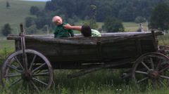 Father and baby son sit together in traditional wooden cart in nature Stock Footage