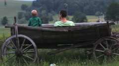 Tender moment, baby son and father relax in wooden traditional cart in nature Stock Footage