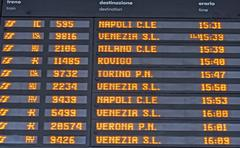 board schedules of arrivals and departures of trains in an italian train stat - stock photo