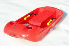 Red plastic bob  for play and to descend from the mountains with snow Stock Photos