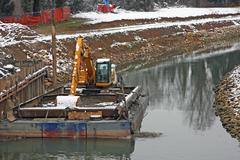 Bulldozer digger in a barge during the work of the river Stock Photos