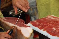 Butcher knife cut large slices of enticing ham to sell Stock Photos