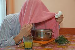 man with pink towel breathe balsam vapors to treat colds and the flu - stock photo
