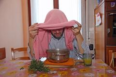 man with pink towel breathe balsam vapors to treat colds - stock photo