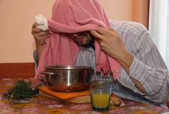 adult man with towel breathe balsam vapors to treat colds and flu - stock photo