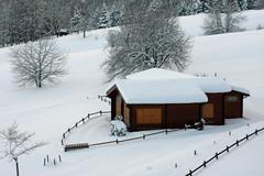 wooden mountain chalet in the alps in italy after a heavy snowfall - stock photo