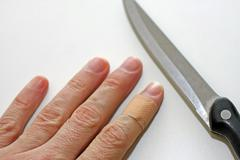 Hand with finger with a band aid and the sharp blade of the knife in the kitc Stock Photos