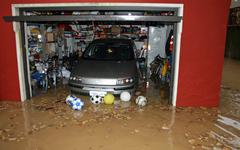 car in the garage of the house submerged by flood mud - stock photo