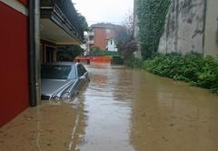 car in the courtyard of the house submerged by flood mud - stock photo