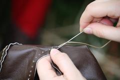 Woman while sewing a dress in leather with needle and thread Stock Photos