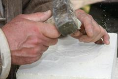 Old craftsman mason during the processing of a piece of white marble Stock Photos
