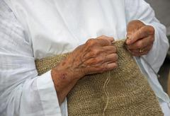 hands of an elderly woman during the processing of wool sweater - stock photo