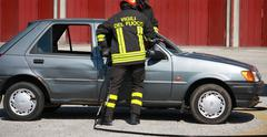firefighters freed a wounded trapped in car after a traffic accident - stock photo