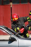 Firefighters freed a wounded trapped in car after a traffic accident Stock Photos
