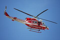 Patrol helicopter of firefighters in blue sky over a fire 4 Stock Photos