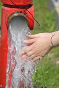 Wash hands under the powerful jet of water from a fire hydrant Stock Photos