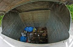 inside a dumpster of trash almost completely empty - stock photo