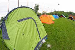 camp with tents scout campers in a green meadow - stock photo
