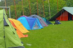 camp with igloo tents scout campers in a green meadow - stock photo