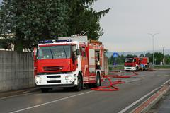 firefighters with the fire truck when switching off a fire - stock photo