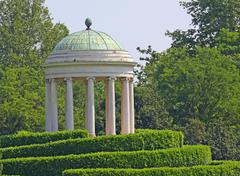 Ancient greek roman-style temple on the hill in the meadow green Stock Photos