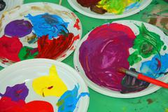 Acrylic color palettes to the nursery during the drawing lesson Stock Photos