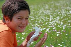 Child with an allergy to pollen while sneeze in the middle of the flowers Stock Photos