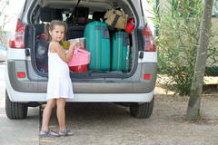 little girl with white dress loads the car - stock photo
