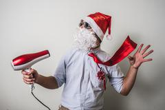 funny santa claus babbo natale with hairdryer - stock photo