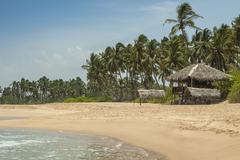 Tropical beach with low key restaurant Stock Photos